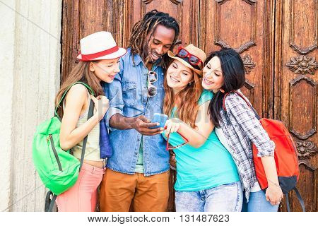 Group of multiracial friends looking mobile phone are traveling around the world - Mixed race students having fun using new smartphone technology - Concept of friendship and happiness - Focus on male
