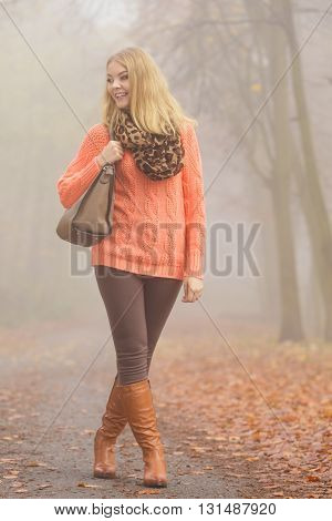 Fashion Woman With Handbag Posing In Autumn Park