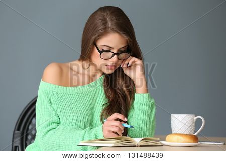 Young attractive woman sitting with notebook on gray background