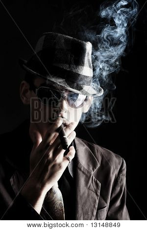 Portrait of a handsome young man in elegant suit smoking a cigar.