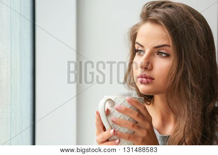 Beautiful young woman holding cup on light background