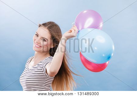 Woman attractive joyful girl playing with colorful balloons. Summer holidays celebration and lifestyle concept. Studio shot blue background