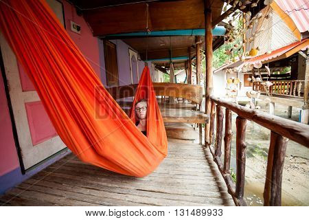 Young woman in hammock on tropical island Koh Phangan in Thailand. Chalokum beach resort.