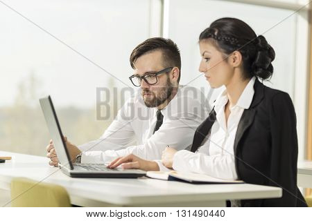 Two business colleagues working on a laptop computer in an office