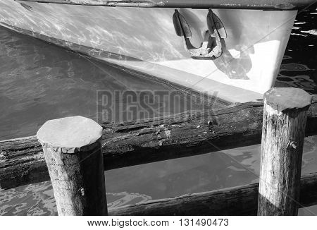 Embankment wooden fence with part of ship and anchor. Wooden embankment fence above lake water in black and white. Part of ship with anchor moored on lake.