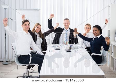 Group Of Smiling Multi Ethnic Businesspeople Raising Arms In Office