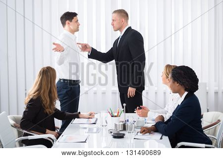 Group Of Businesspeople Looking At Businessman Blaming His Colleague In Meeting