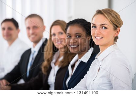 Happy Multiethnic Businesspeople Sitting In Row In Office