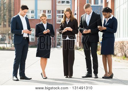 Group Of Multi-racial Businesspeople Using Mobile Phones;Outdoor