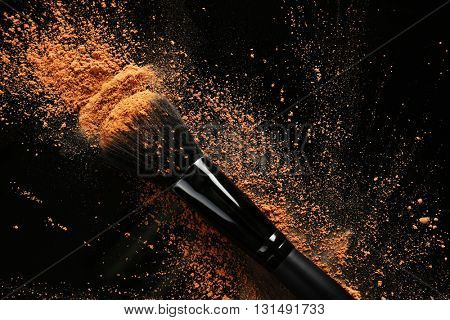 Makeup brush with cosmetic powder on dark background
