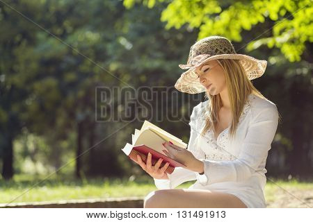 Young woman reading a book on a sunny summer day in the park