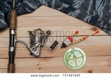 Set for fishing on the wooden background with camouflage clothing. Coil colored floats fishing line. Fishing.