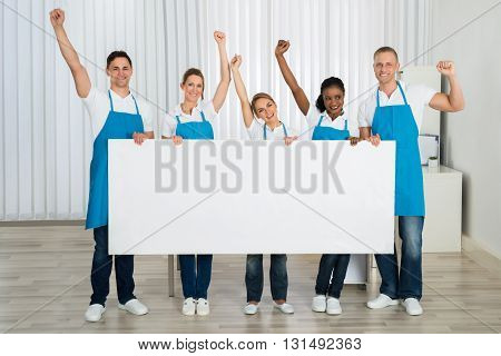 Group Of Happy Janitors Cheering While Holding Blank Billboard In Office
