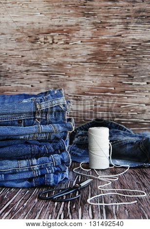 stack of jeans lying on a wooden table, sewing machine and supplies for sewing, selective focus