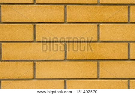 New flat brick wall of beige color with deep seams.