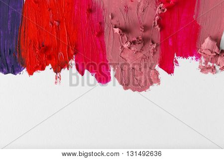 Smudged colourful lipstick on white background, close up