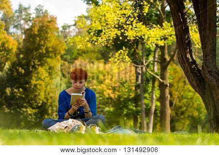 Girl reading a book. / Red-haired girl reading a book on a glade in the park.