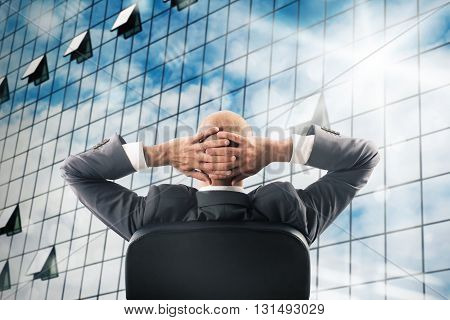 Man sitting relaxed watching a mirrored skyscraper