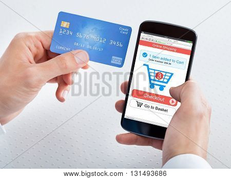 Close-up Of A Person's Hand Holding Mobile Phone Shopping Online With Credit Card