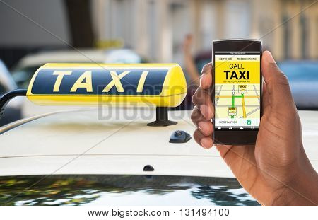 Close-up Of A Person's Hand Booking Taxi On His Mobile Phone