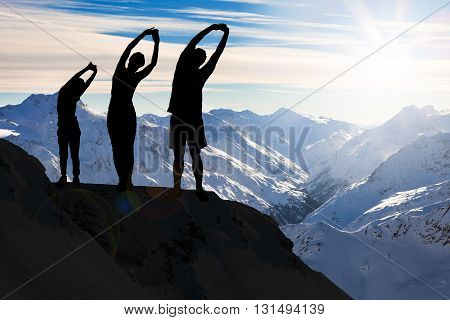 Silhouette Of A Family Stretching On A Cliff Against Snowy Mountains