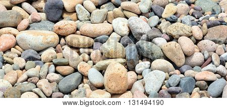 Mixed little brown and grey stones on the beach