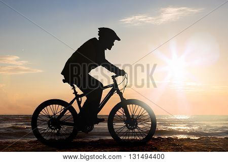 Silhouette Of A Man Cycling At Beach During Sunset