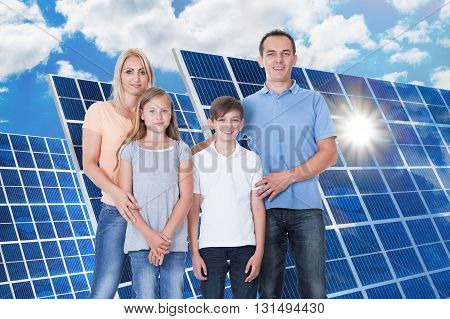 Portrait Of A Smiling Family Standing In Front Of Solar Panel