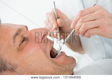 Mature Man Examined By Dentist In Clinic