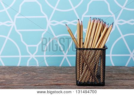 Pencils in metal holder on the table, closeup
