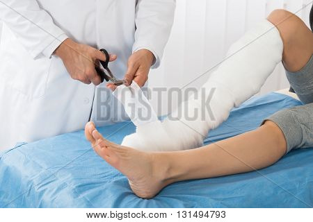 Doctor Bandaging Leg Of Patient In Hospital