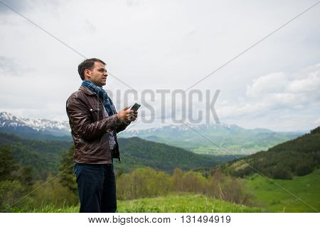 Happy man holding tablet in nature. Outdoors shot in the mountains