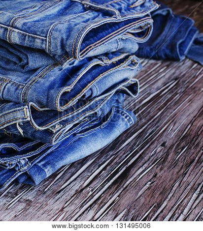 stack of jeans lying on a wooden table, selective focus