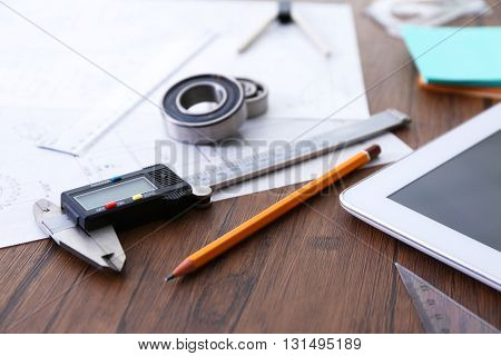 Engineering supplies and tablet on wooden background
