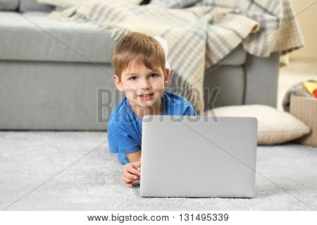 Little boy using laptop on carpet indoors