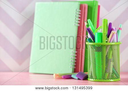 Stationery in metal holder on color background