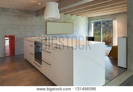 Interior of a modern chalet in cement, white kitchen island