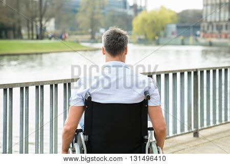 Rear View Of Disabled Man On Wheelchair Looking At Lake