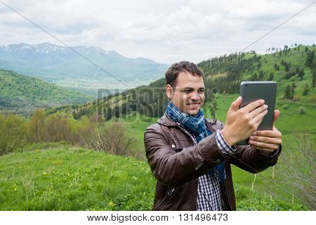 Young man holding digital tablet in front of him in nature.