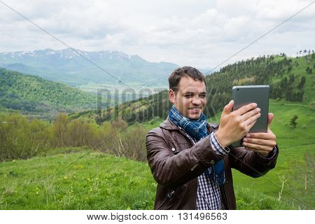 Amazing man taking selfie with digital tablet in the mountains.