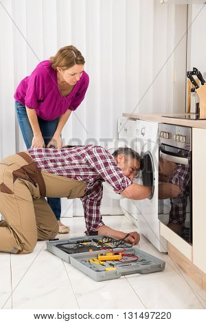 Woman Looking At Male Technician Fixing Washing Machine In Kitchen