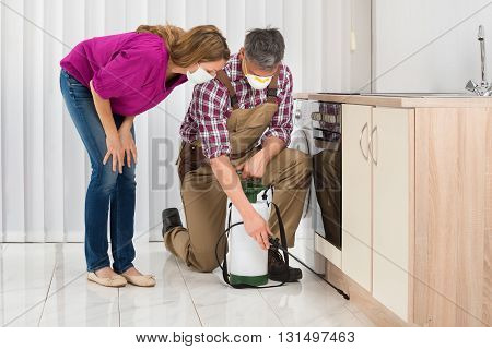 Mature Woman Looking At Male Worker Spraying Insecticide In Kitchen