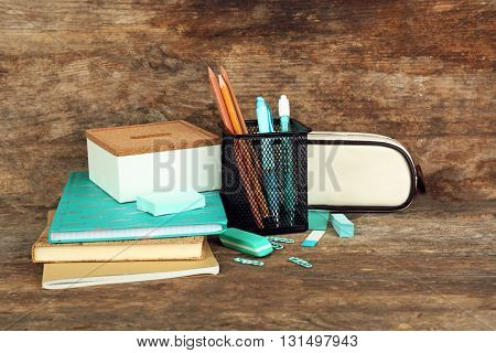 School supplies on old wooden table, close up