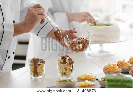 Male chef  pouring chocolate  sauce over a fruit dessert.