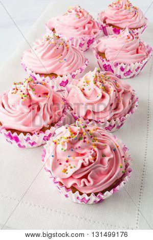 Pink cupcakes on the linen napkin. Birthday cupcakes. Homemade cupcake. Sweet cupcake. Gourmet cupcakes. Sweet pastry. Sweet dessert.