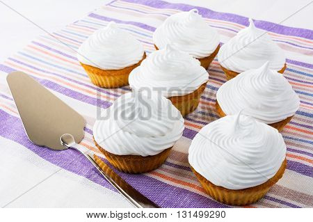 White cupcakes on the striped napkin. Birthday cupcakes. Homemade cupcake. Sweet cupcake. Gourmet cupcakes. Sweet pastry. Sweet dessert.