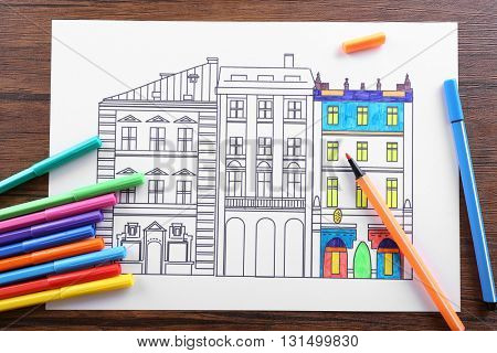 Adult anti stress coloring with soft tip pencils on wooden table, top view