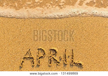 April - written by hand on a golden beach sand.