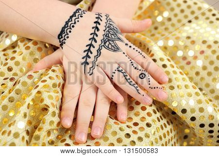 Henna ornaments on girl's hand on color cloth background