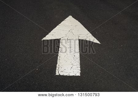 Old, painted, white arrow on the road